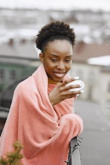 테라스에서 아프리카 소녀입니다. 분홍색 격자 무늬에 커피를 마시는 여자. 사진을 위해 포즈를 취하는 여자.