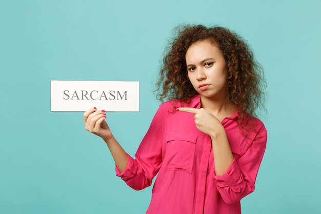 African girl in pink casual clothes pointing index finger on text board sarcasm isolated on blue turquoise wall background in studio. people sincere emotions, lifestyle concept. mock up copy space.