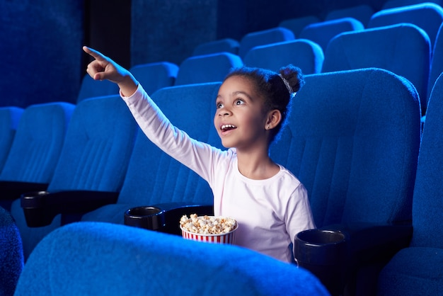 African girl poiniting with finger at screen in cinema.