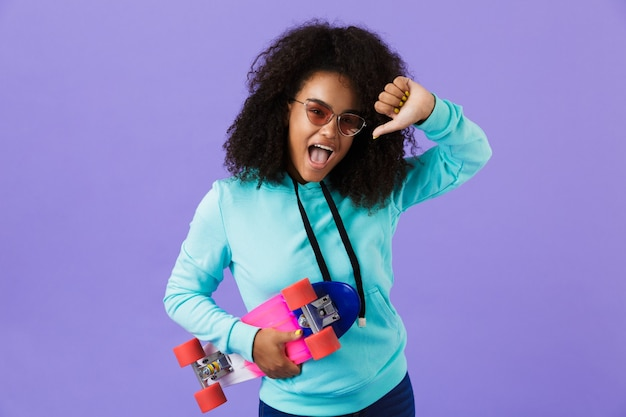 African girl posing isolated over violet space holding skateboard showing thumbs down.
