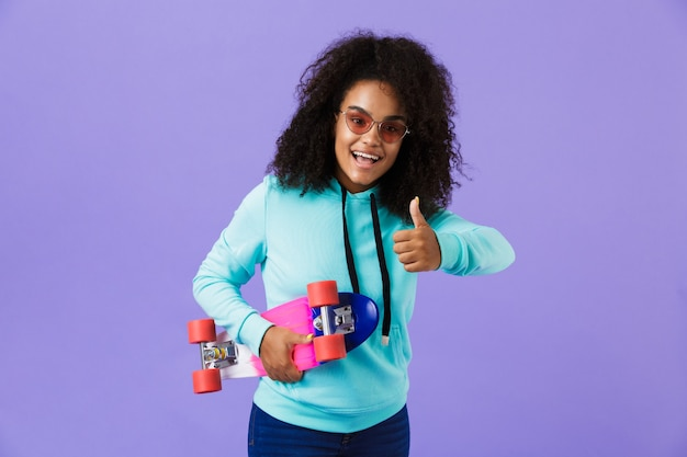 African girl posing isolated over violet space holding skateboard.