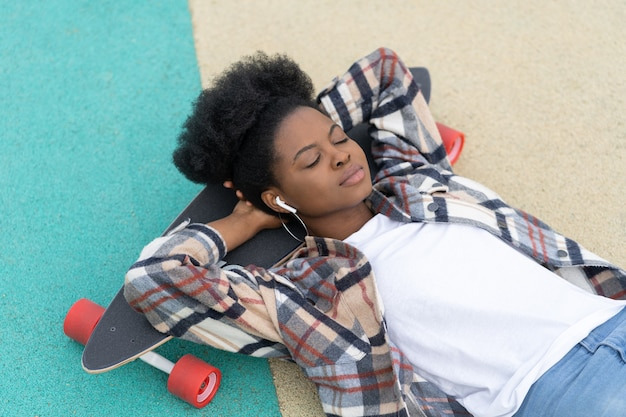 African girl relaxed lying on longboard listen music in wireless earphones with closed eyes outdoors