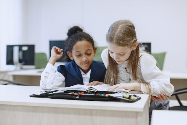 テーブルに座っているアフリカの女の子。女子学生は休憩中に本を読みます。子供たちはコンピュータサイエンスのクラスに座っています。