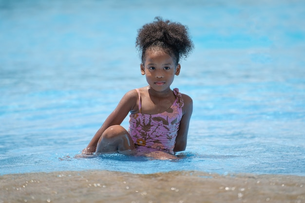 African girl sitting and playing water in swimming pool at amusement park.
