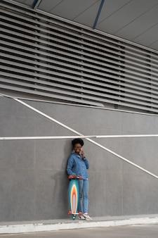 아프리카 소녀 스케이팅은 건물 벽 근처에 롱보드가 있는 스마트폰 스탠드를 들고 전화를 걸다
