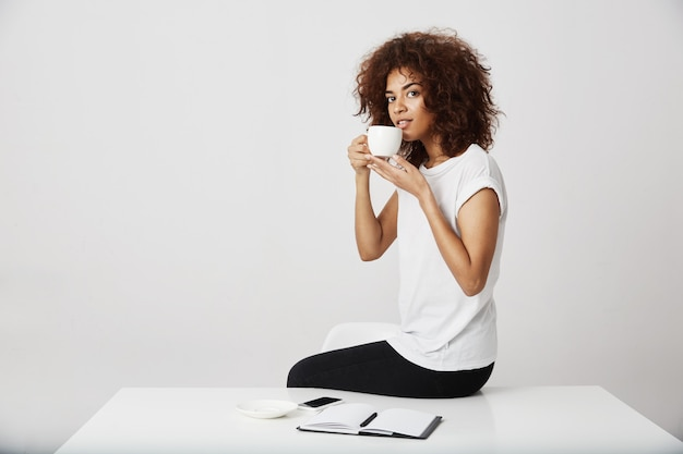 African girl smiling drinking tea sitting on table over white wall.