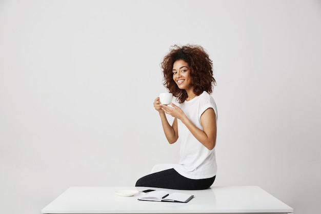 African girl smiling holding cup sitting on table over white wall.