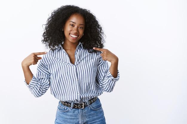 Ragazza africana che suggerisce aiuto per promuovere le proprie capacità di essere pro che si indica con orgoglio sorridente denti bianchi dall'aspetto amichevole testa inclinabile in piedi fiducioso audace ambizioso, parete dello studio