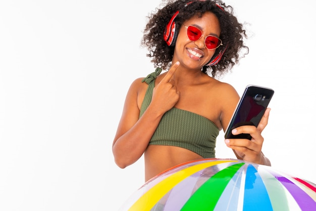 African girl in sunglasses and a swimsuit holds the phone in her hands and listens to music