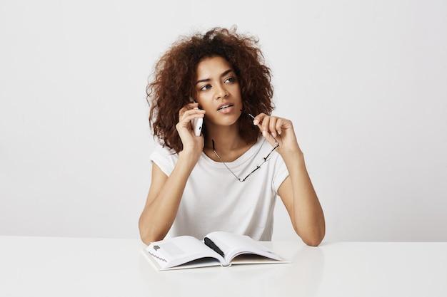 白い壁の上のテーブルに座って電話思考で話しているアフリカの女の子。コピースペース。