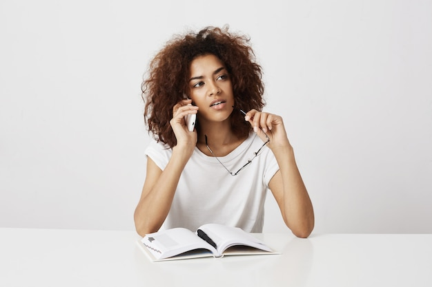 African girl talking on phone thinking sitting at table over white wall. copy space.