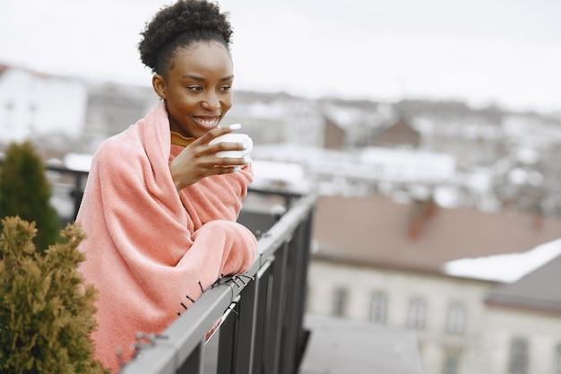 Ragazza africana sulla terrazza. donna che beve il caffè in un plaid rosa. signora in posa per una foto.