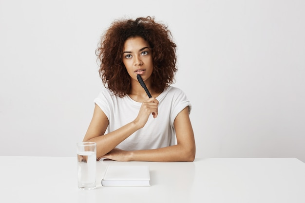 African girl thinking sitting at table over white wall. copy space.