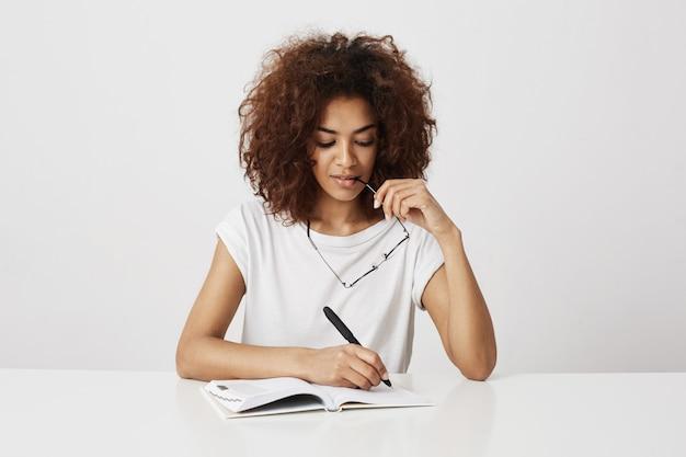 白い壁に笑みを浮かべてノートに書いて考えてアフリカの女の子。コピースペース。
