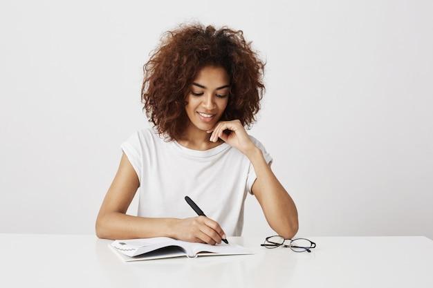 认为在笔记本的非洲女孩写在白色墙壁上。复制空间。