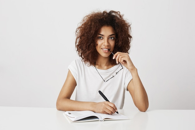 African girl thinking writing in notebook smiling over white wall. copy space.