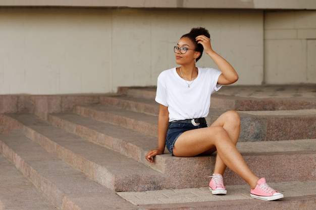 African girl in a white t-shirt and glasses sits on the steps. summer