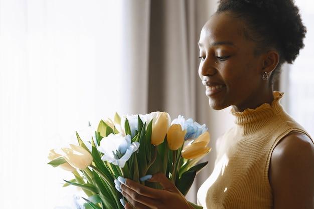 花とアフリカの女の子。手にチューリップの花束。窓際の女性。