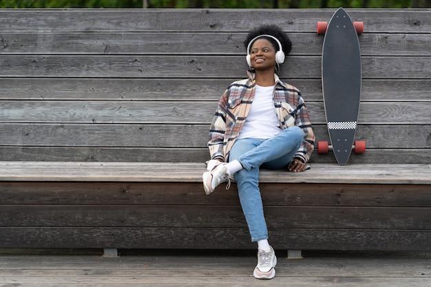 롱보드를 탄 아프리카 소녀는 야외 공원에서 스케이트보드를 탄 후 행복한 미소를 지으며 음악을 듣습니다.