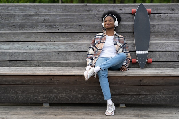 African girl with longboard listen music with happy smile after skateboarding chill in park outdoor
