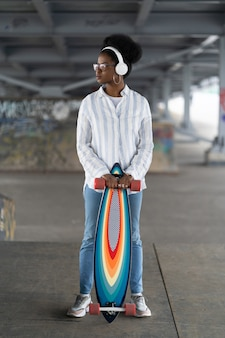 African girl with skateboard trendy female dressed in urban outfit wear headphones hold longboard