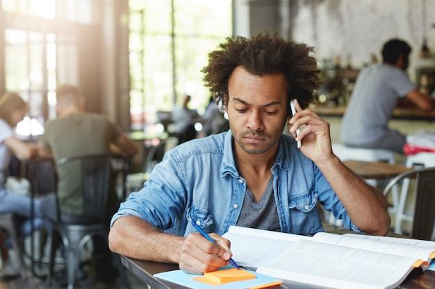 黒い肌と豊かな髪を持つアフリカの大学院生の男性が彼の卒業証書用紙で働いて、スマートフォンで彼の研究監督者に相談しているカフェの木製の机に座っている重要なアイデアを書き留めている