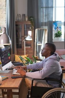 自宅でオンラインで作業しているコンピューターモニターの前で車椅子に座っているアフリカのグラフィックデザイナー