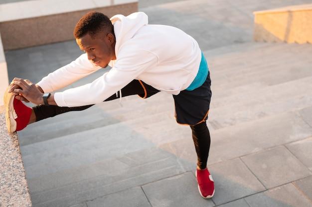 활성 복을 입은 아프리카 남자가 대리석 계단에 서서 도시 환경에서 훈련하는 동안 뻗은 다리로 앞으로 구부립니다.