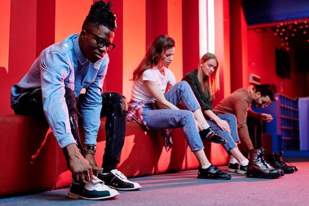 黒のジーンズとデニムシャツを着たアフリカ人の男が壁に沿って赤い革のベンチに座って、試合前にボウリングの靴を履いています
