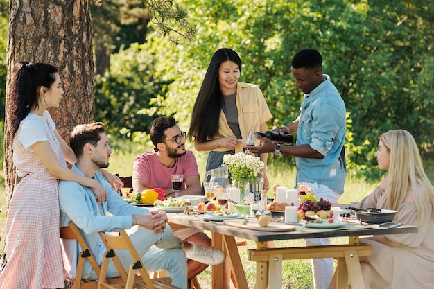 Африканский парень в джинсовой рубашке и белых джинсах наливает красное вино в бокал для одной из девушек во время ужина на открытом воздухе у обслуживаемого столика в парке