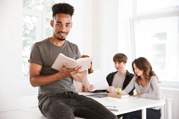 Африканский парень, читающий книгу