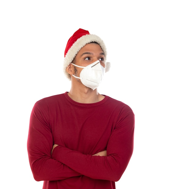 African guy wearing a christmas hat and a mask isolated on a white background