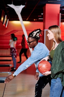 African guy with stretched arm explaining his girlfriend how to throw bowling ball on track or alley while playing at leisure center