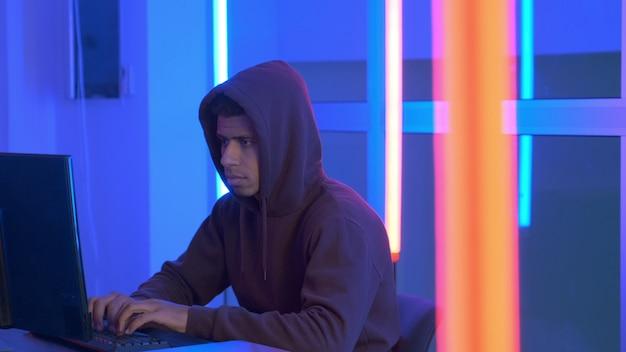 Африканский хакер одет в толстовку с капюшоном работает на компьютере