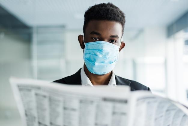 事務所ビルで新聞を読んで医療マスクでアフリカのハンサムなビジネス男