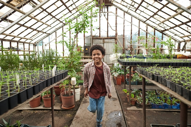 African happy boy running along the road among green plants in greenhouse