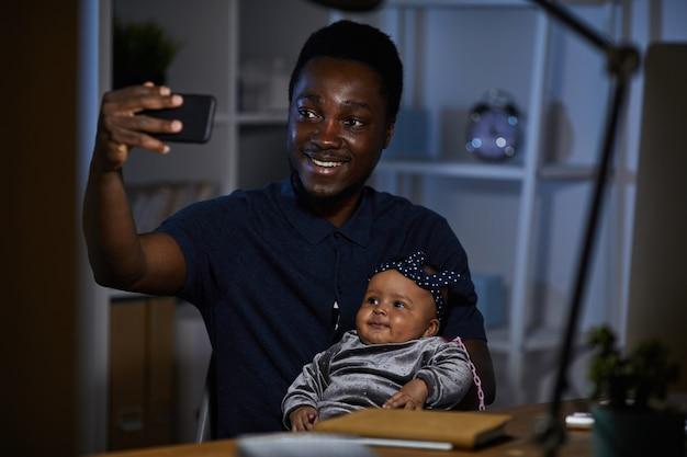 Африканский счастливый отец делает селфи со своей маленькой дочкой на мобильном телефоне, сидя за столом
