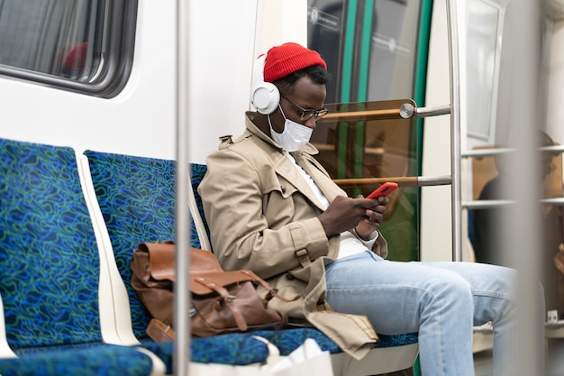 African hipster man in subway train wear face mask using cellphone listens to music with headphones.