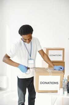 보호 장갑에 아프리카. 남자는 상자를 포장합니다. 인도 주의적 지원으로 자원 봉사하십시오.