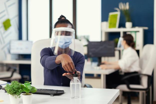 코로나바이러스로 전 세계적으로 유행하는 동안 소독제를 사용하는 직장에서 아프리카. 동료들이 백그라운드에서 일하는 동안 소독하는 새로운 일반 직장의 사업가입니다.