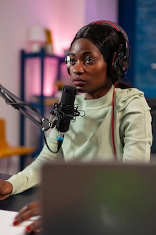 청취자를 위해 마이크에 대고 이야기하면서 질문에 답하는 아프리카 인플루언서. 라이브 스트리밍 중 연설하는 블로거는 헤드폰을 끼고 팟캐스트에서 토론합니다.
