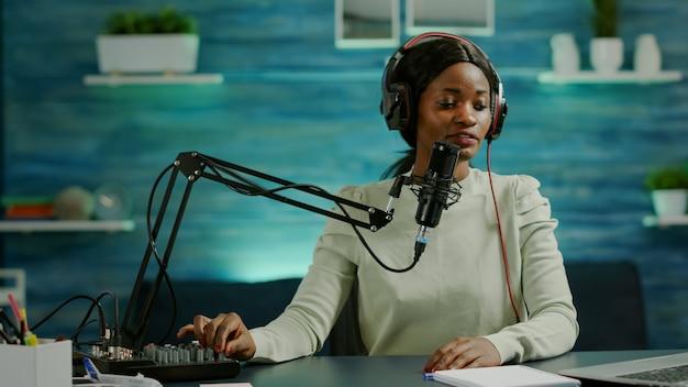 홈 스튜디오에서 전문 사운드 믹서와 마이크를 사용하여 콘텐츠를 녹음하는 아프리카 인플루언서. 라이브 스트리밍 중 연설하는 블로거는 헤드폰을 끼고 팟캐스트에서 토론합니다.