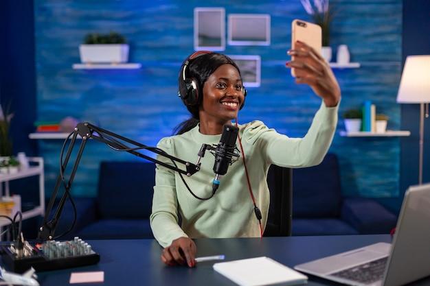 아프리카 인플루언서가 동영상 블로그를 녹화하면서 청취자를 위해 셀카를 이야기하고 있습니다. 온에어 온라인 제작 인터넷 팟캐스트 쇼 호스트 스트리밍 라이브 콘텐츠, 디지털 소셜 미디어 녹음.