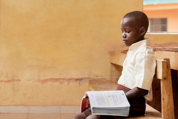 African kid leaning in class