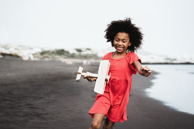 African kid running on the beach while playing with wood toy airplane - focus on face