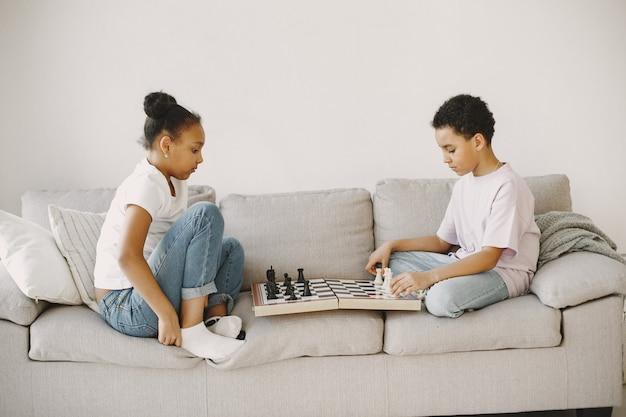 소파에 아프리카 아이. 체스 게임. 곱슬 머리를 가진 아이들.