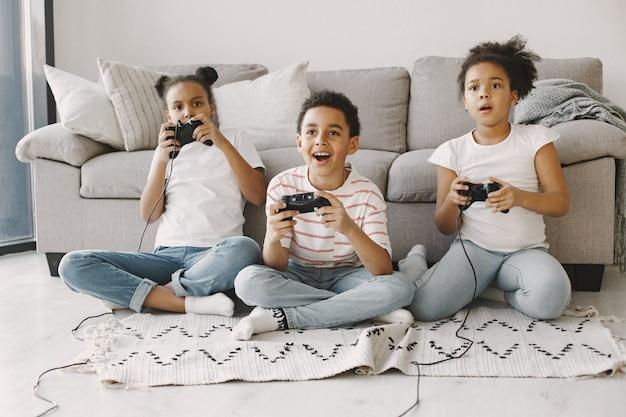 비디오 게임을하는 아프리카 아이들. 가벼운 옷을 입은 아이들. 어린이의 손에 컨트롤러.