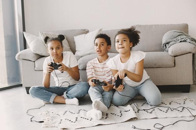 Африканские дети играют в видеоигры. дети в легкой одежде. контроллер в руках детей.