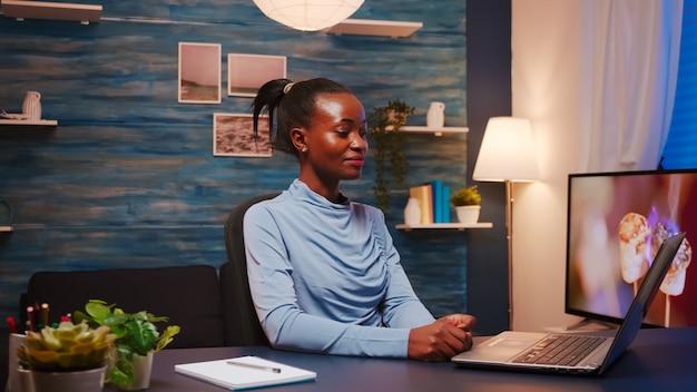 在宅勤務のコンピューターの前に座ってウェビナー中にルールを説明するアフリカの女性。仮想オンライン会議を開催しているビジネスリモートチームと話し合っている黒人従業員。