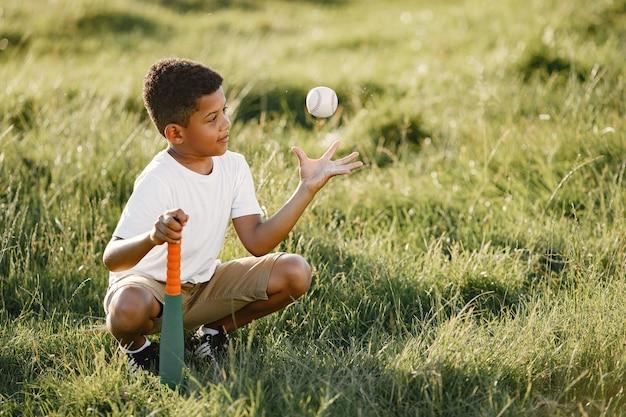 アフリカの小さな男の子。サマーパークの子供。子供はアメリカンフットボールで遊ぶ。